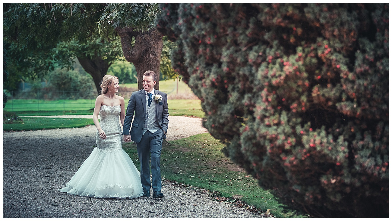Bride and groom walk through the gardens at Gosfield hall smiling and holding hands