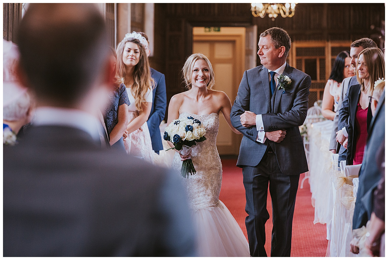 Dad looks at smiling bride as they walk down the aisle