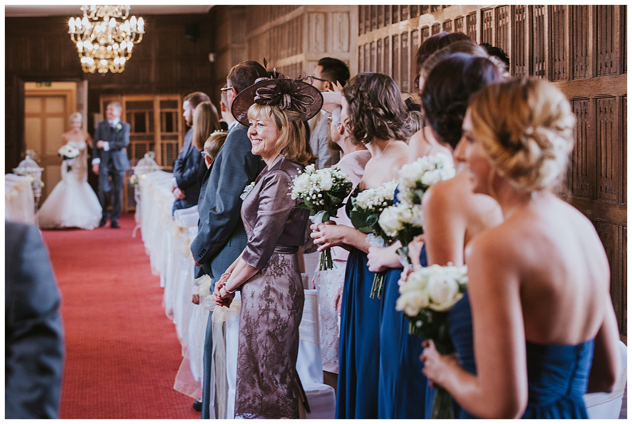 bride enter the room with her dad as the guests smile and look on