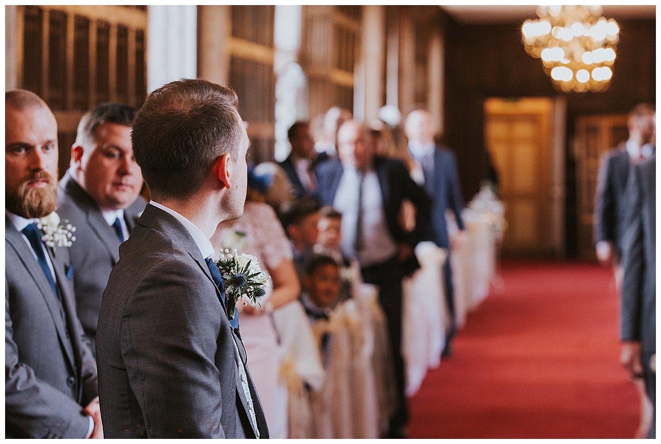 Groom looks back down the aisle and waits for the bride