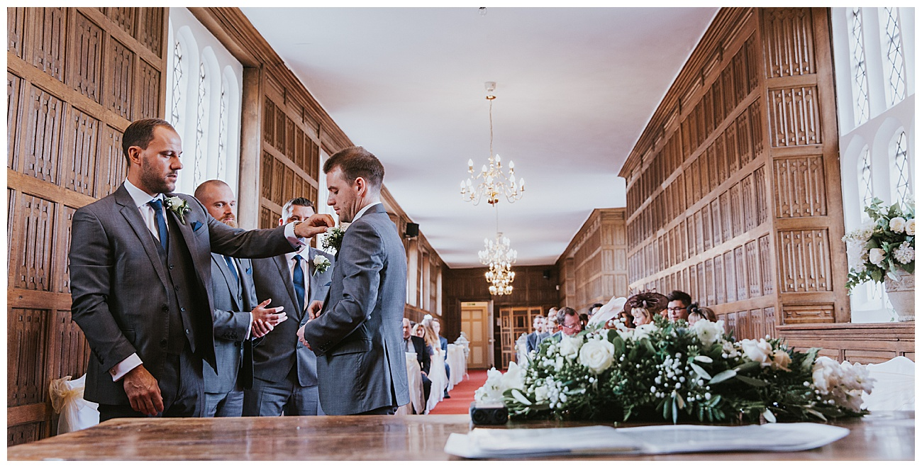 The best man helps with the finishing touches as they stand at the alter