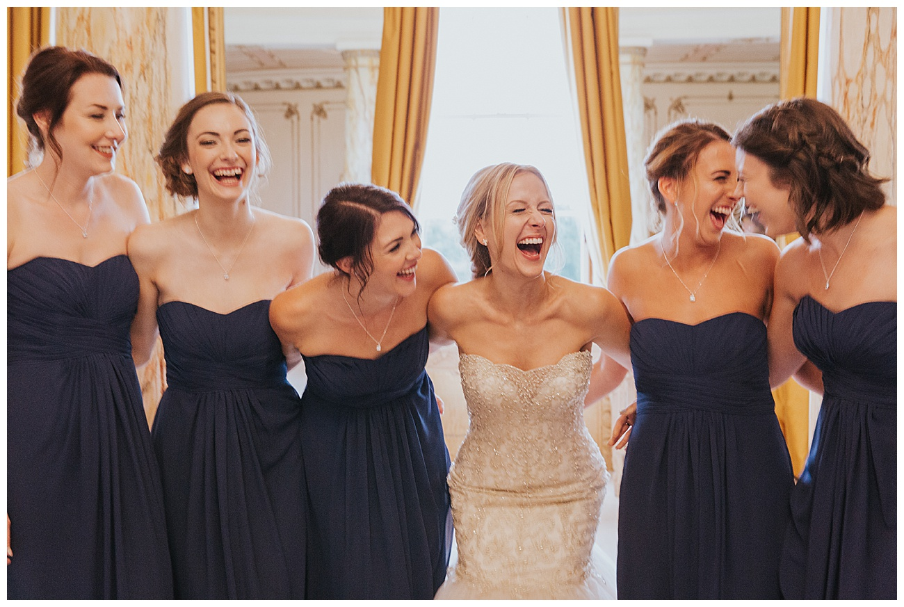 Bridal party share a joke linking arms