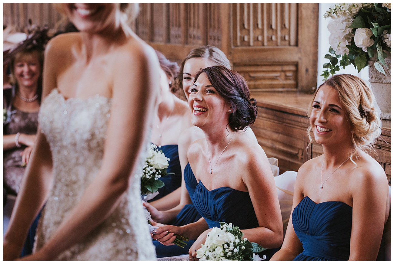 Bridesmaids laugh during the ceremony
