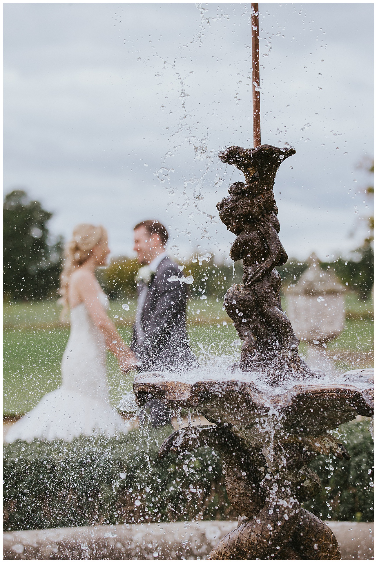 bride and groom hold hands behind a water feature