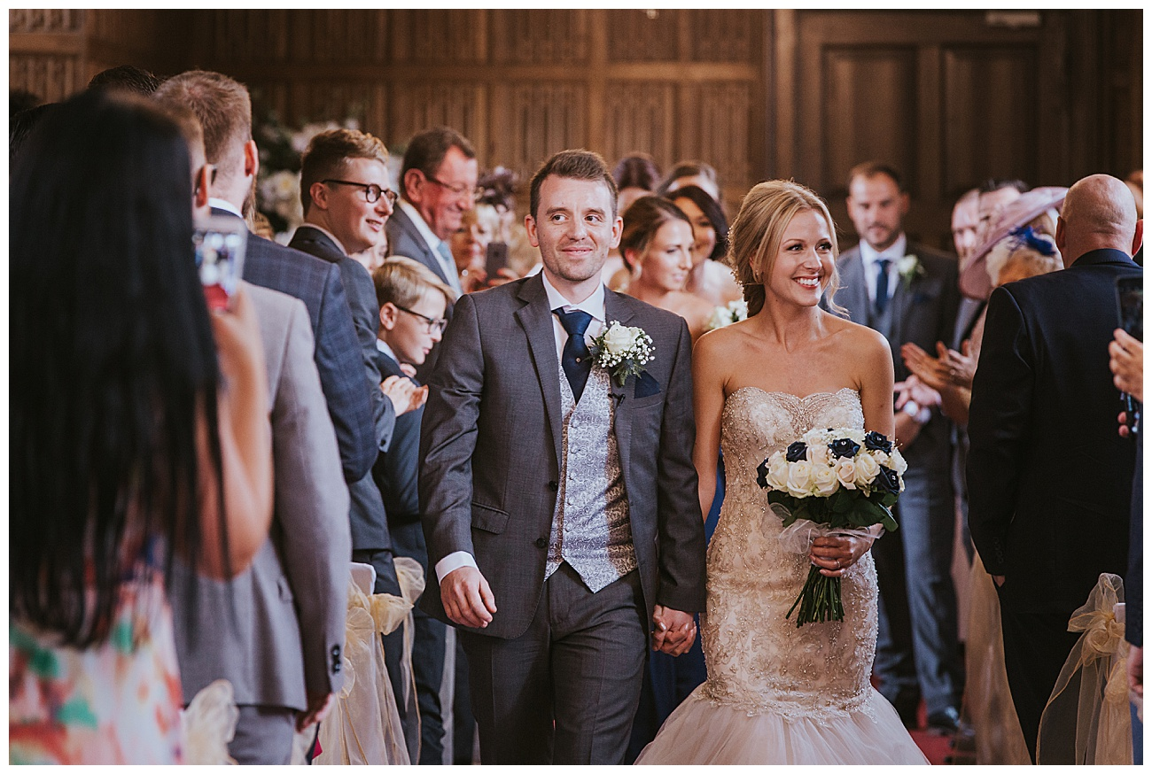 A smiling couple walk back down the aisle past all the wedding guests