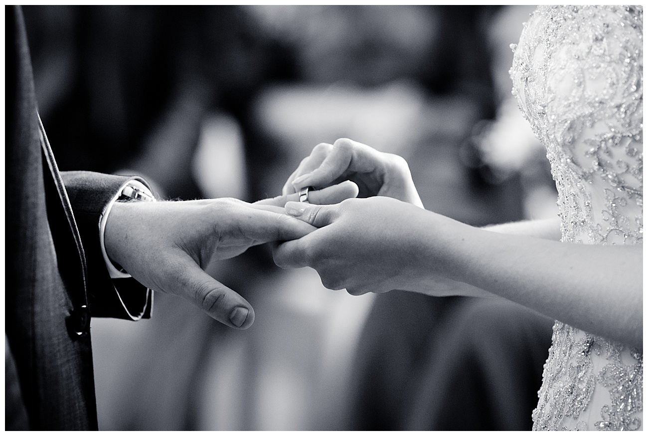 bride puts the wedding ring on the grooms finger