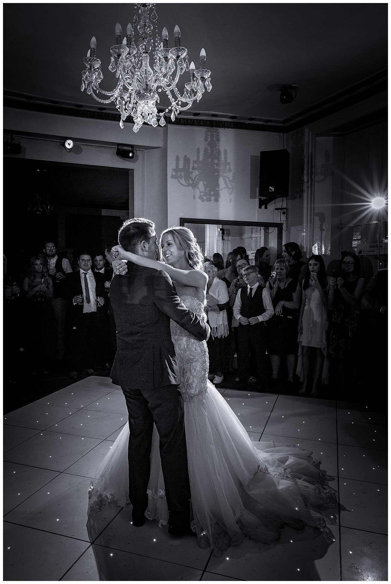 Bride wraps her arms around the groom during the first dance