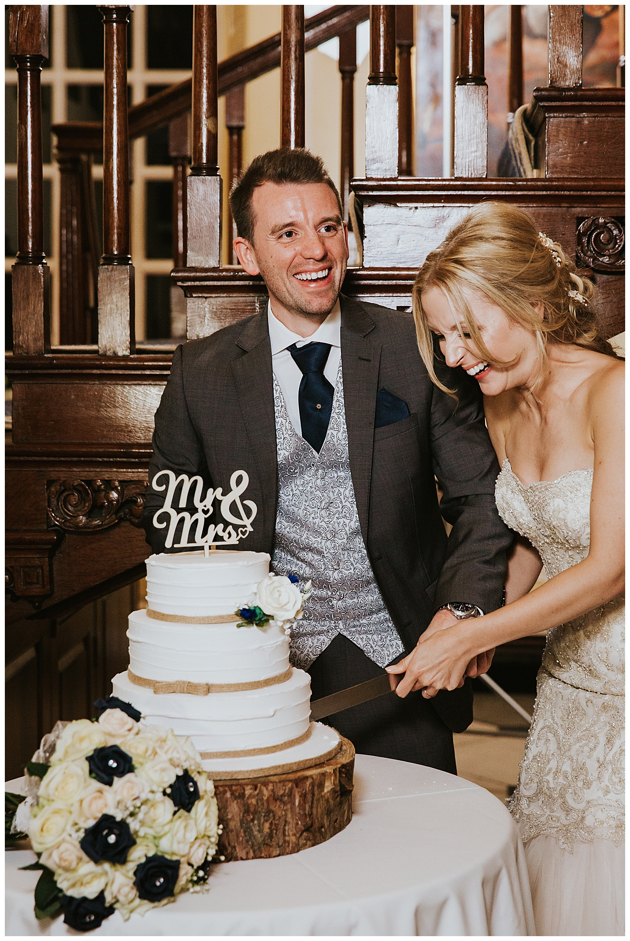 The bride and groom laugh while cutting the cake