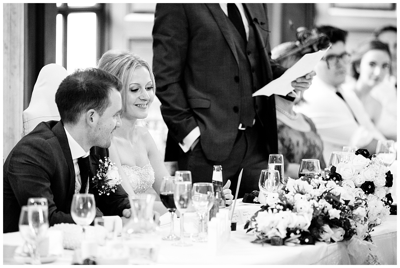 The bride and groom smile at a speech