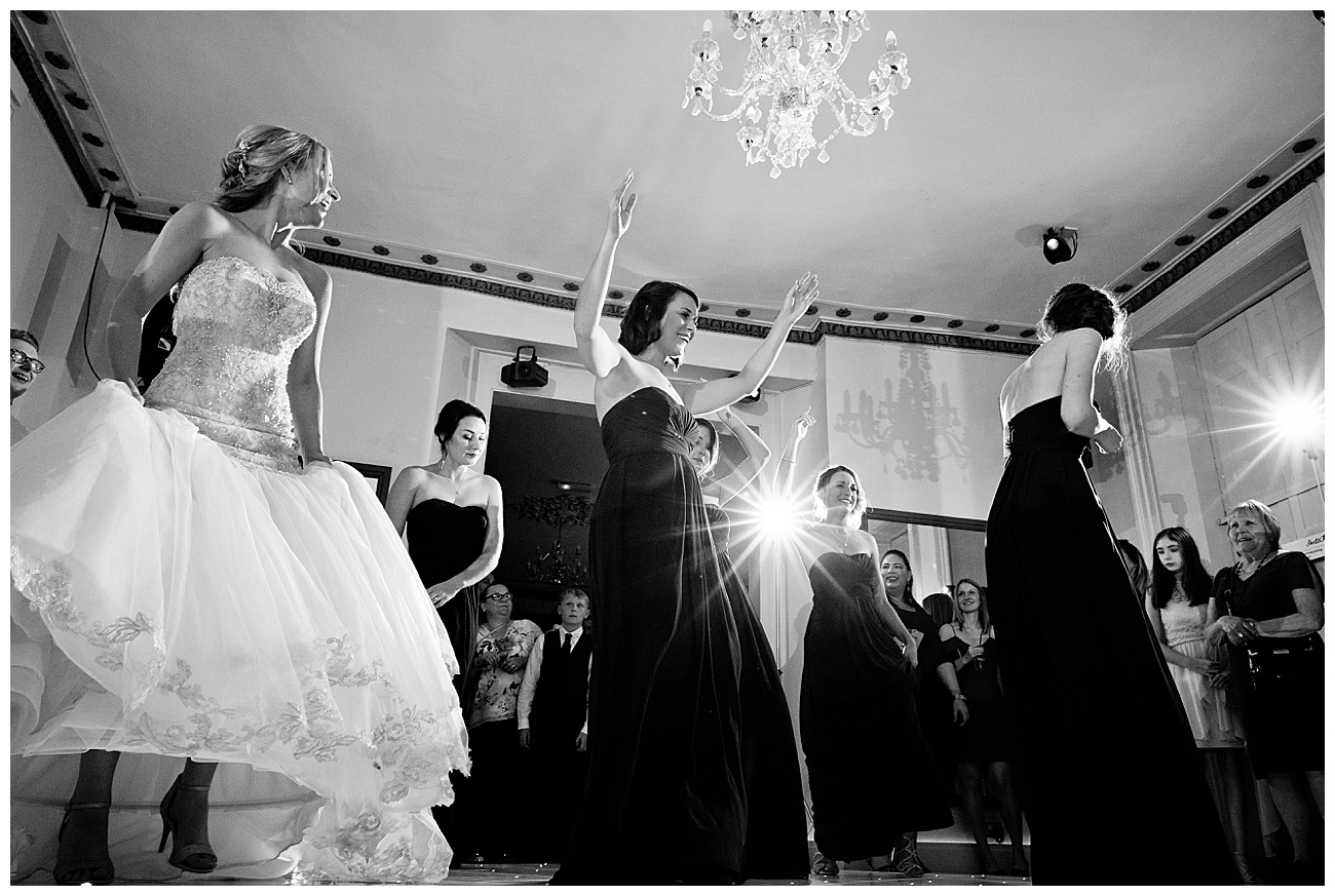 black and white image of the bridal party dancing to a song on the dancefloor