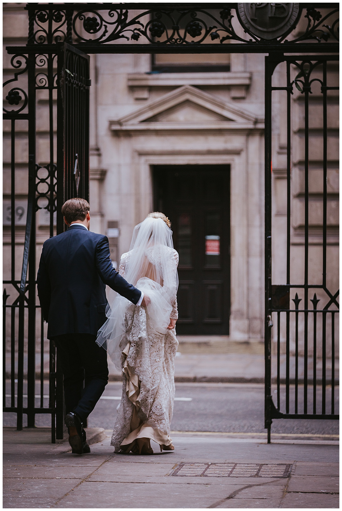 The groom holds the brides dress as they walk through the gates outside Gibson hall