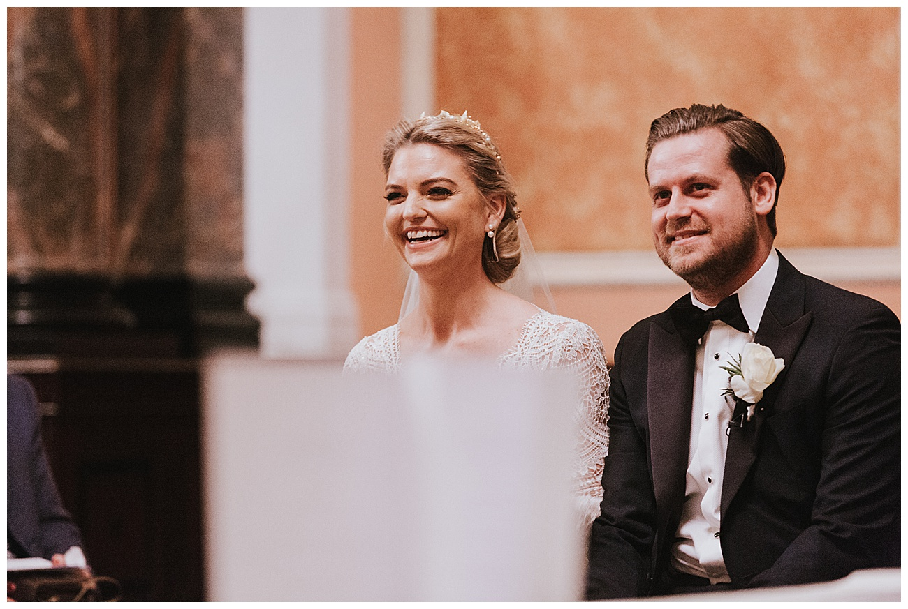 Bride and groom laugh as they sit down to sign the register