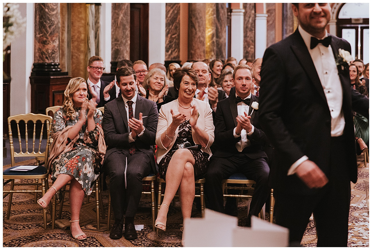 The happy wedding guests clap as the bride and groom are pronounced husband and wife