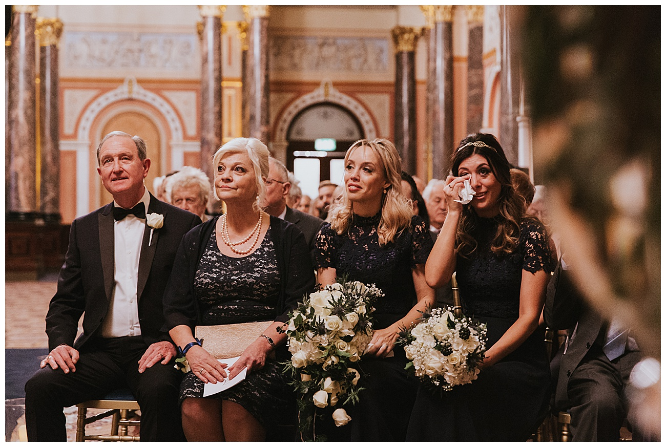 The emotional bridesmaids shed a tear during the ceremony sitting next to the brides mum and dad