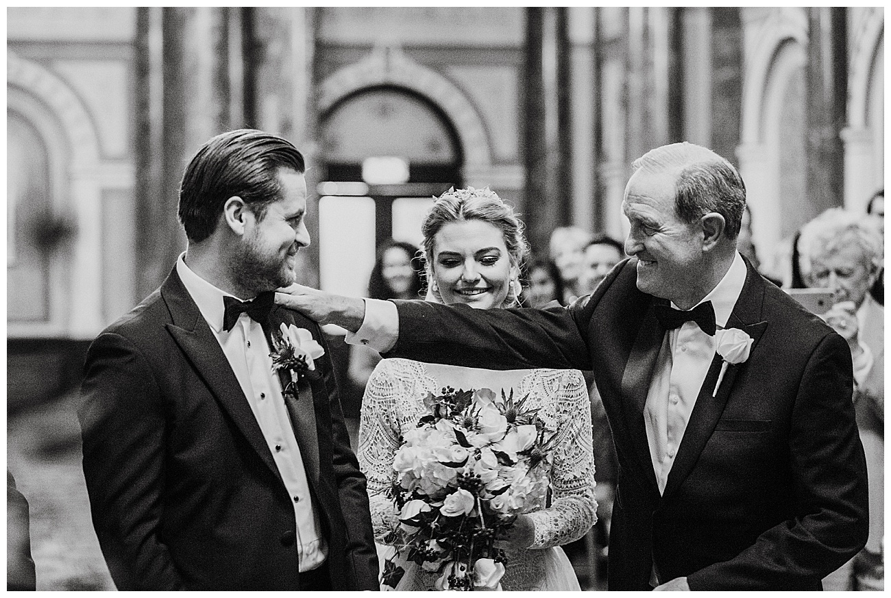 The brides dad places his hand on the grooms shoulder as he hands his daughter over to him at the alter