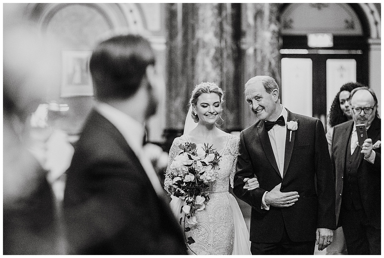 The bride and her dad share a joke and laugh on their way to the alter