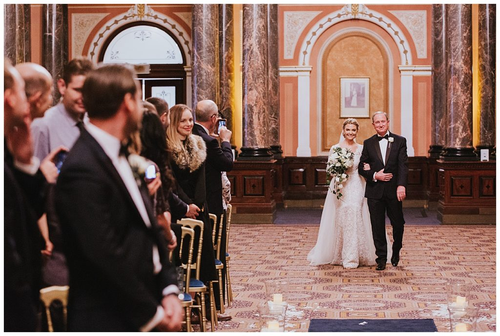 The bride and her dad walk down the aisle as the groom sees her for the first time