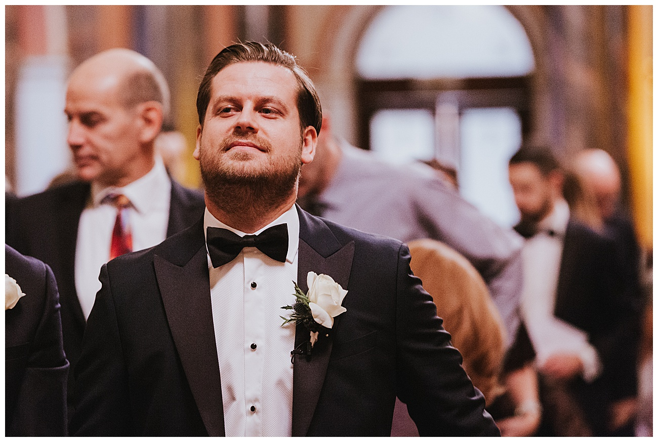 A nervous looking groom at the alter waiting for the bride to enter