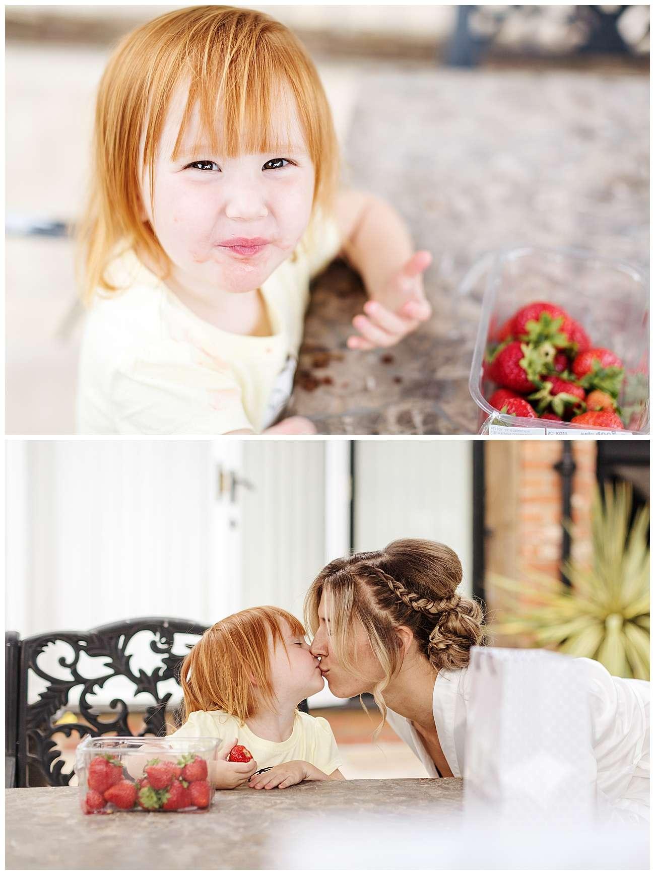 The little flower girl enjoys eating strawberries in the bridal cottage garden
