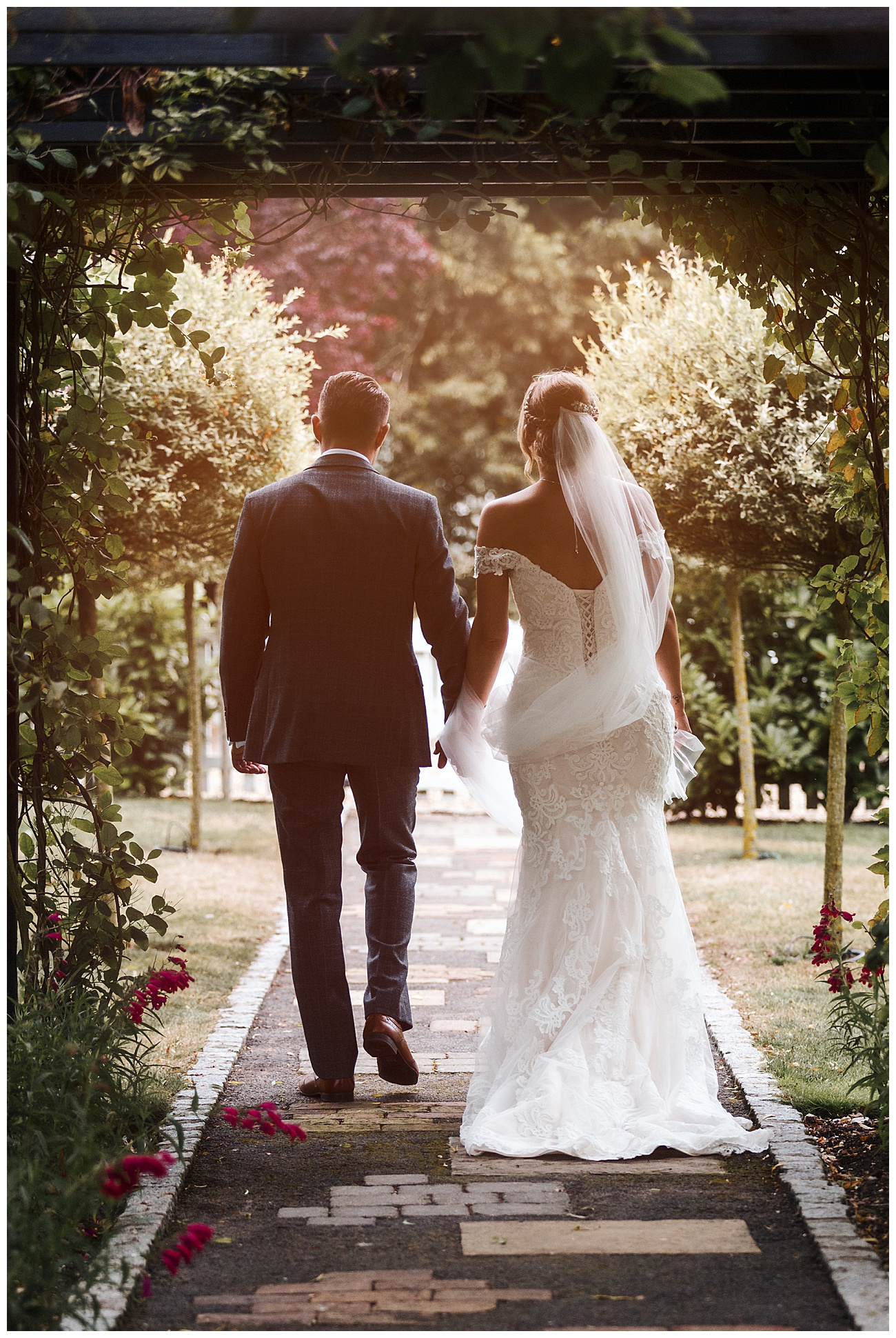 The bride and groom walk away from the camera and through the gardens