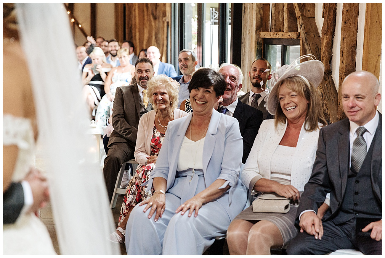 Wedding guests laugh during the ceremony