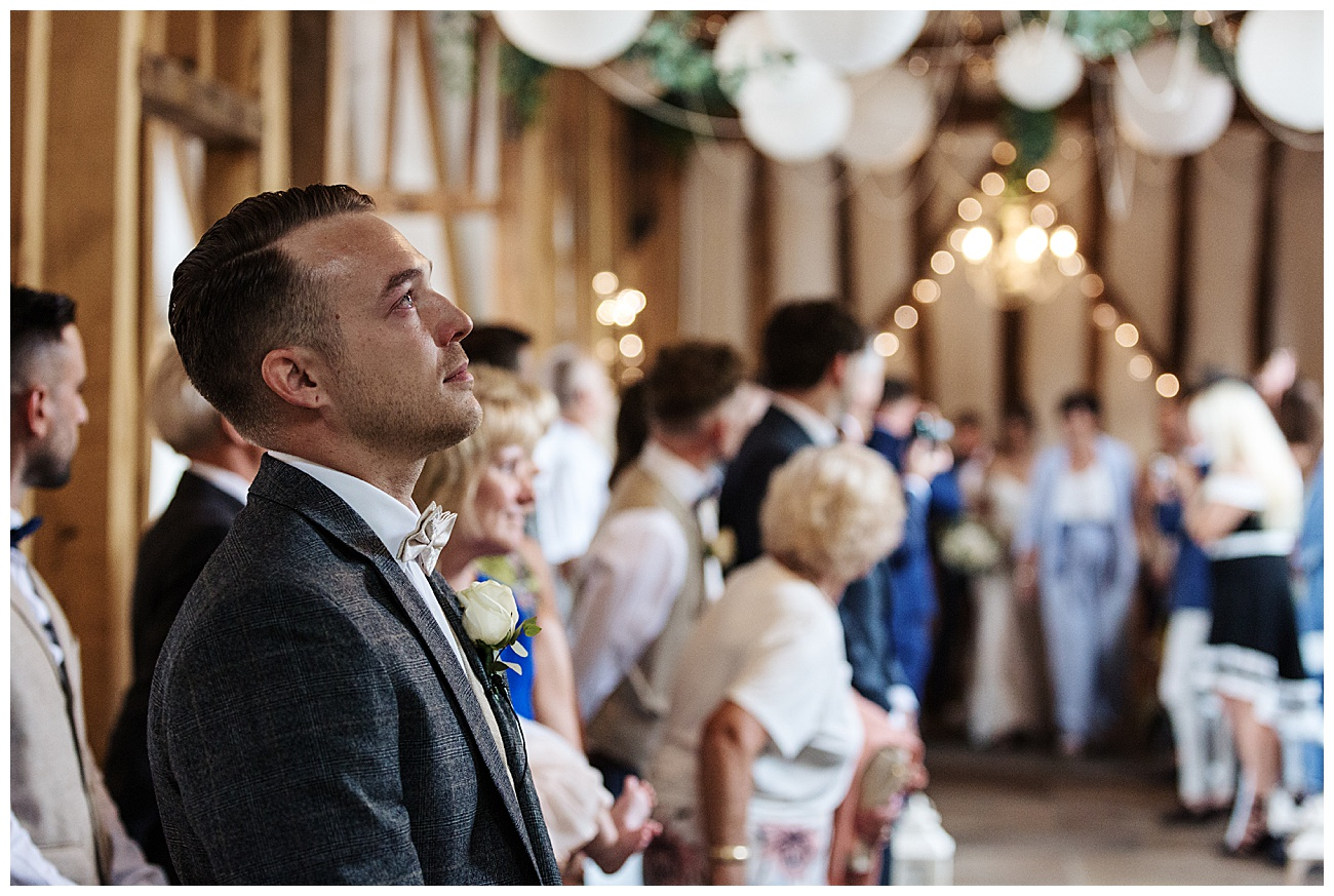 The groom looks nervous and up in the air as the bride enters the ceremony room