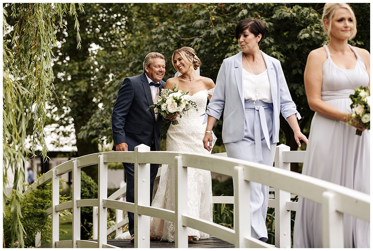 Bride and her dad laugh as they walk across the white wooden bridge on their way to the ceremony