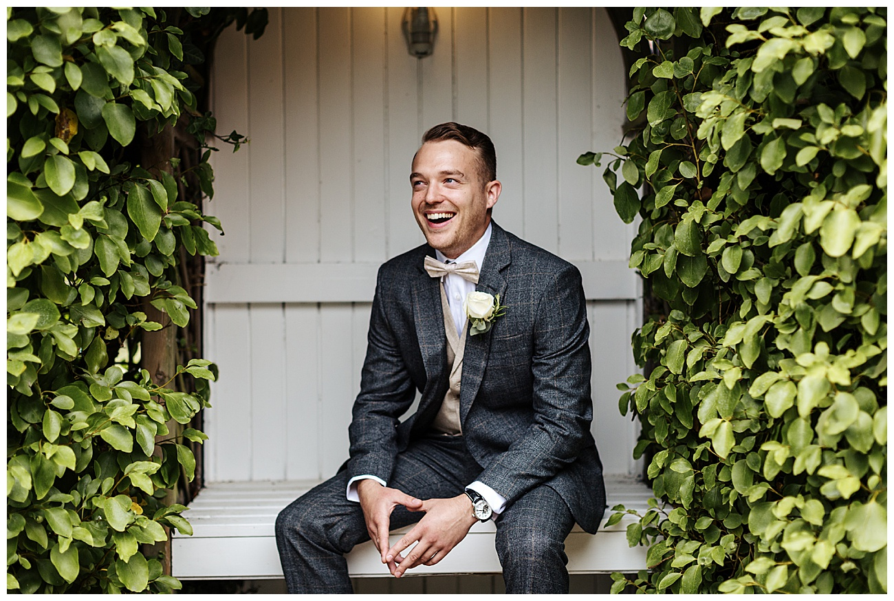 Groom sits down in the garden and smiles in his wedding suit
