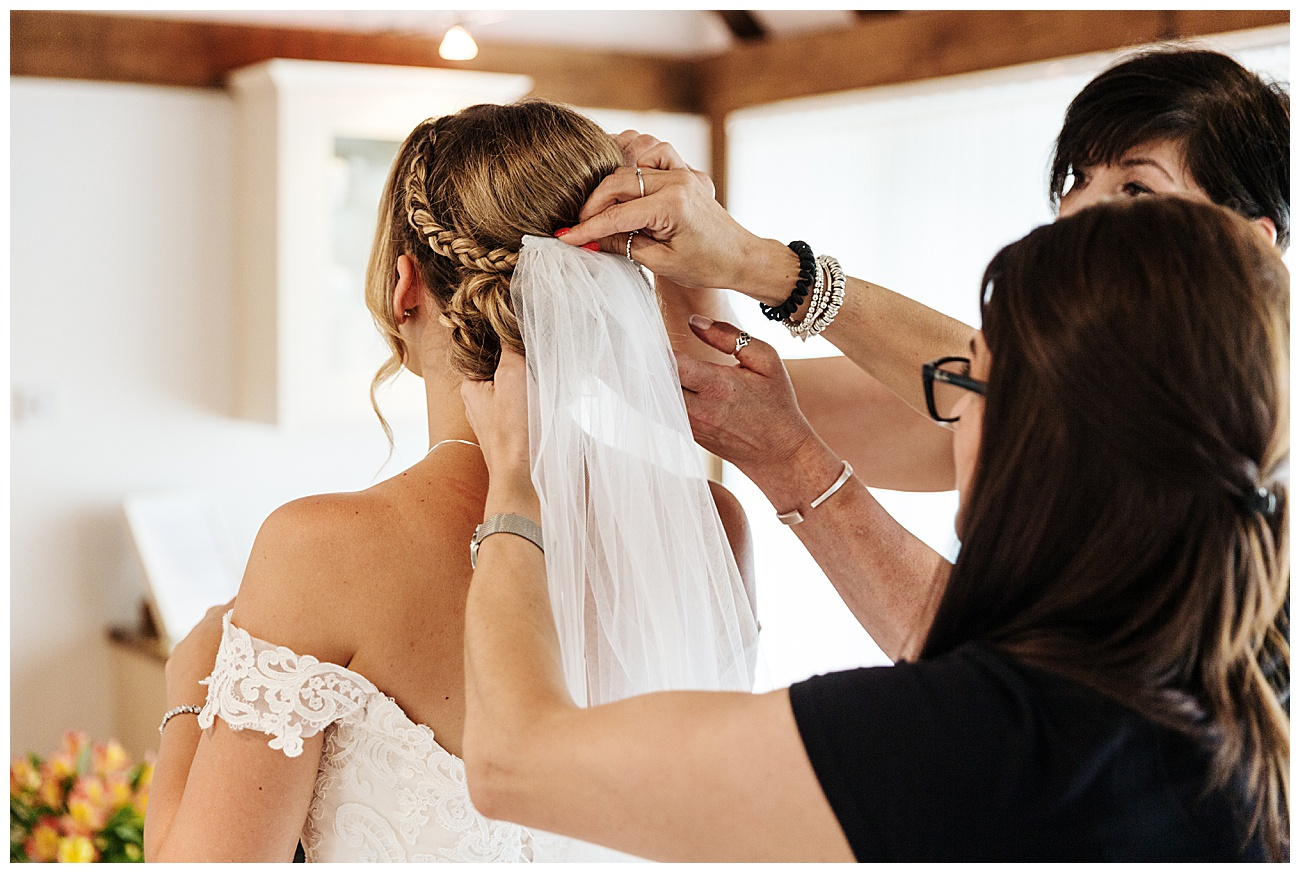 The brides veil is being put into the brides hair by her mum and hairstylist