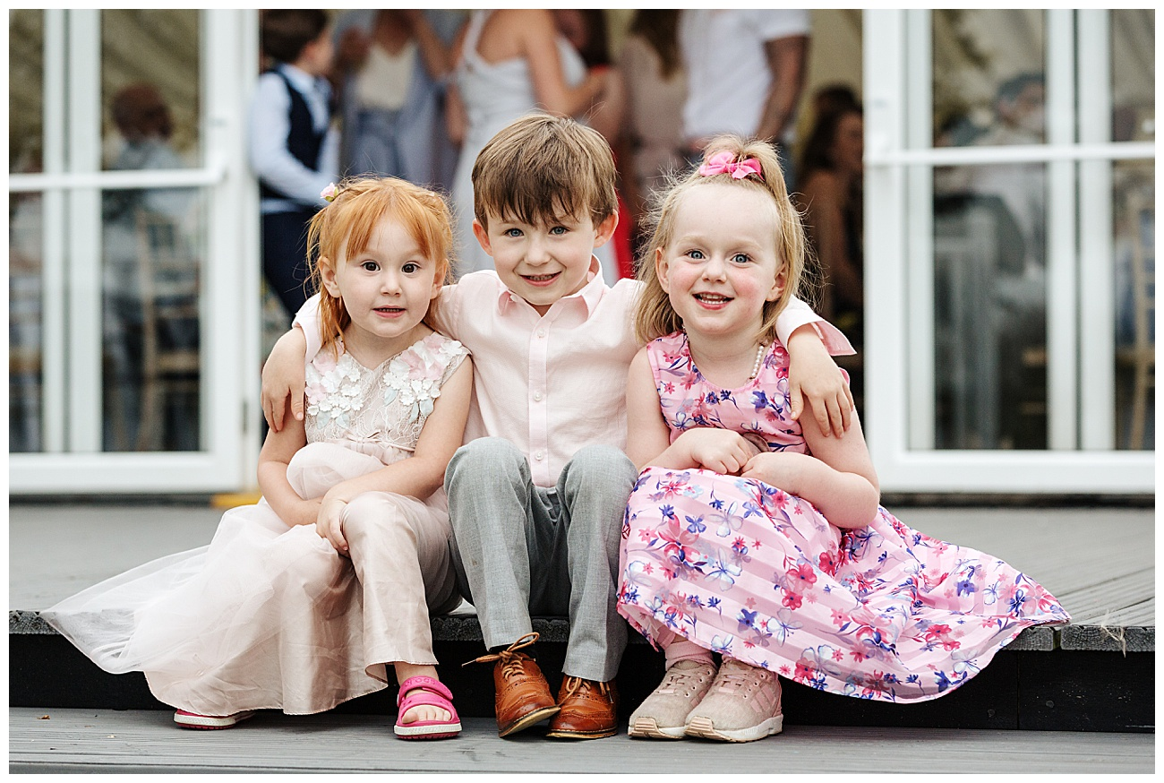 3 young children sit posing for the camera