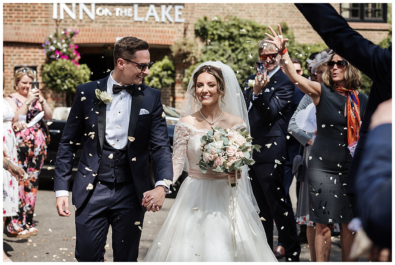 confetti shot as the bride and groom walk past their wedding guests