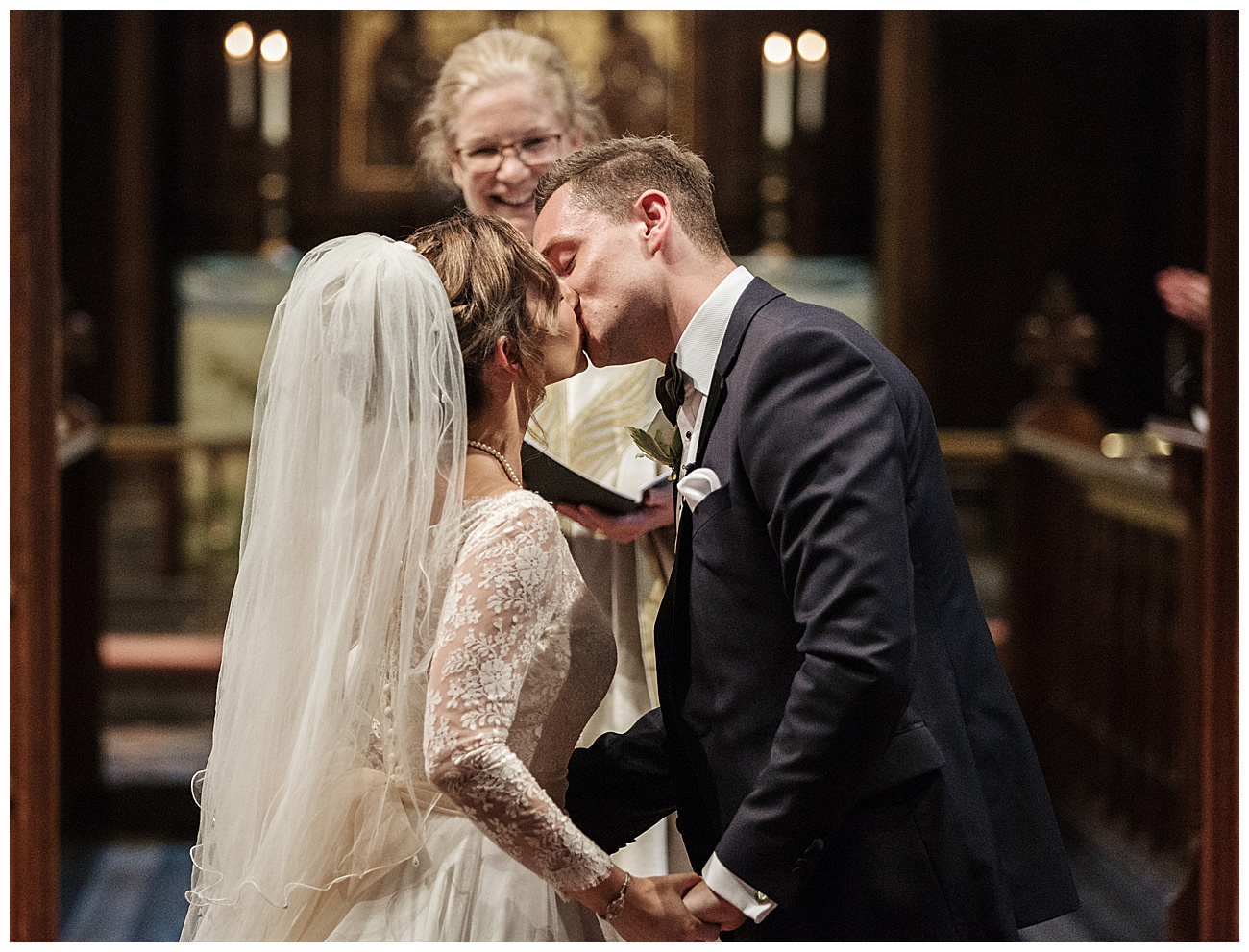 bride and groom kiss at the alter