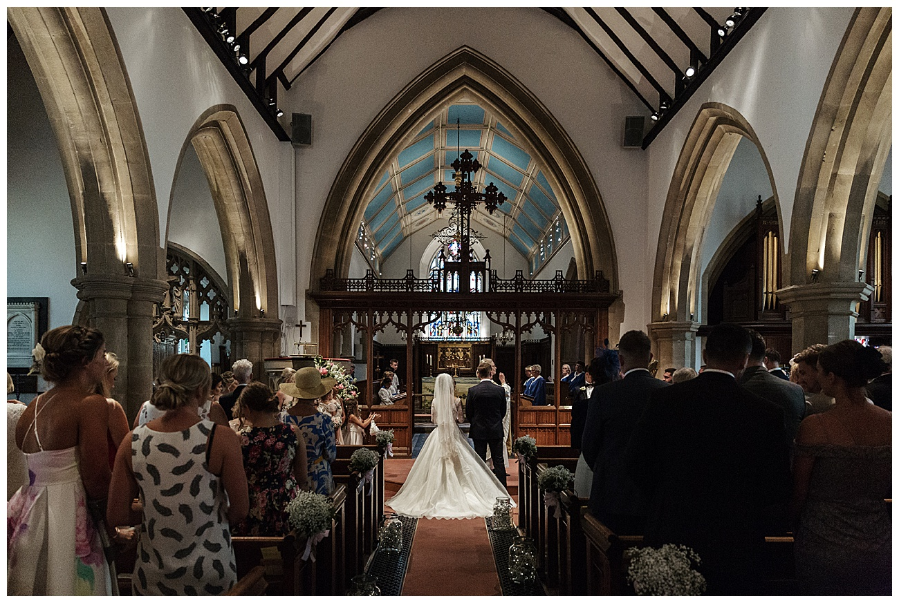 rear view shot of the bride and groom at the later in church