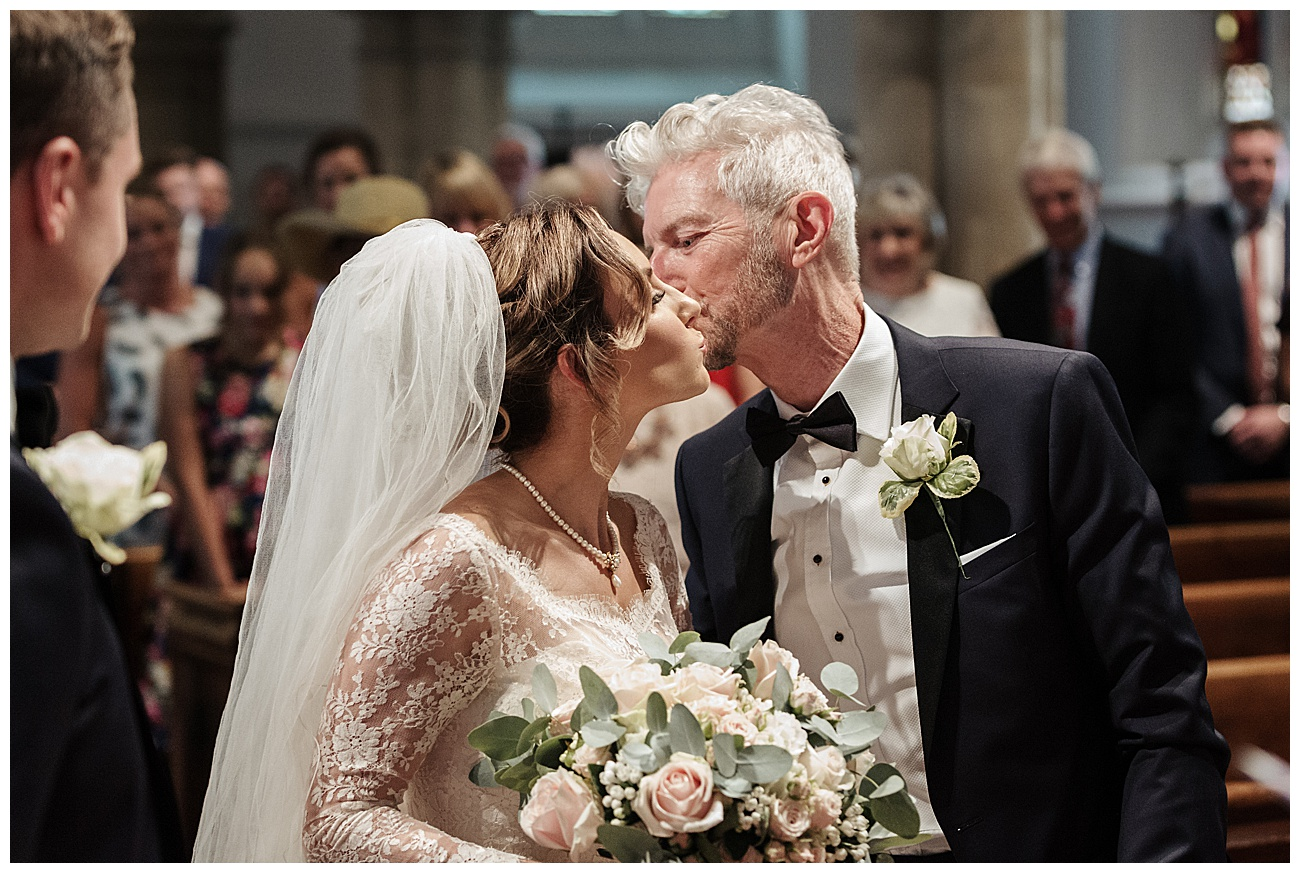 dad gives bride a kiss on the cheek at the alter