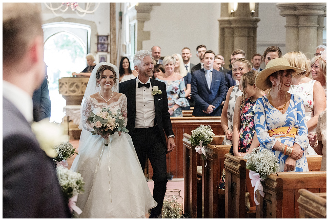 bride and dad walk down the aisle in the church as the groom looks towards them