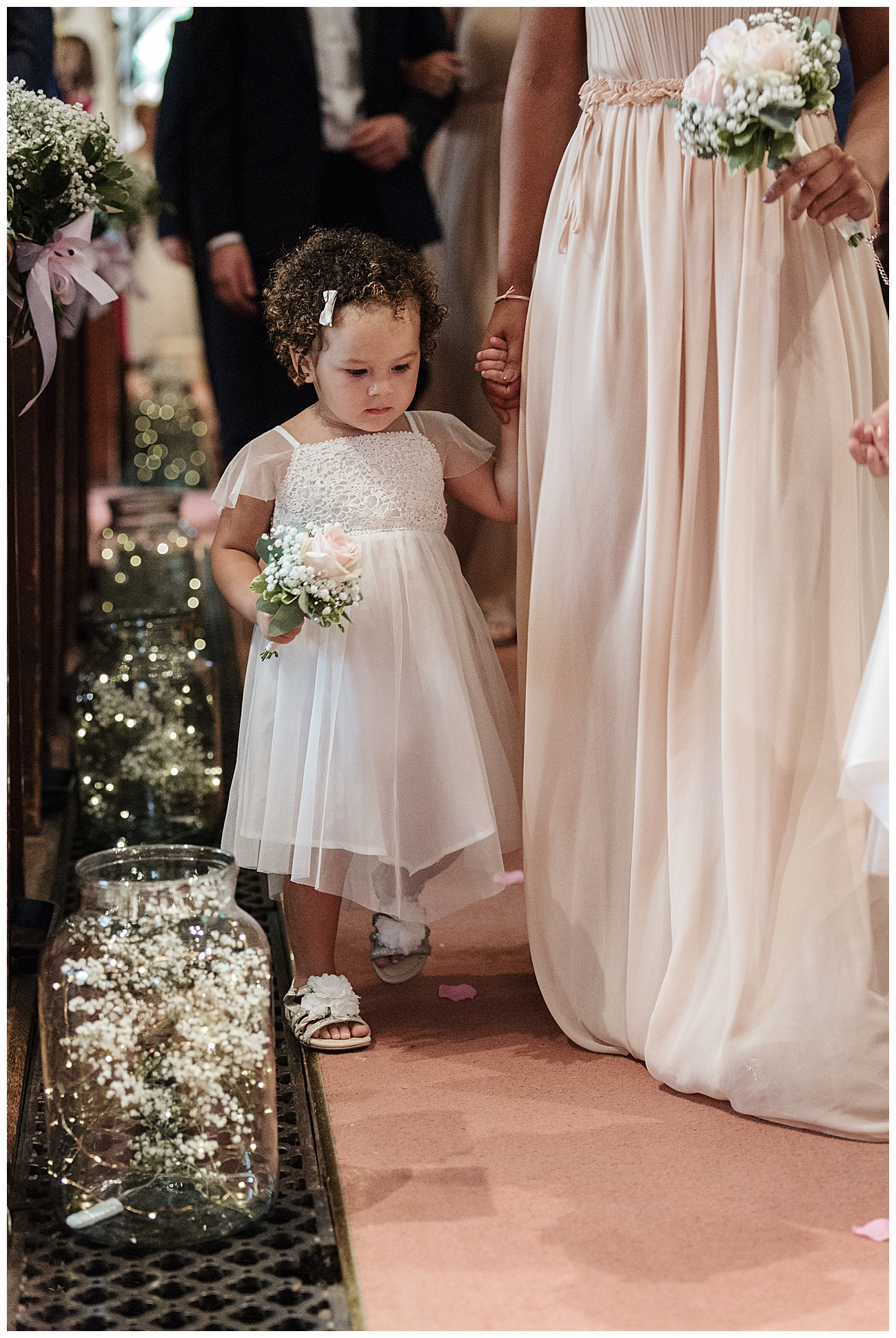 flower girls walks down the aisle at church