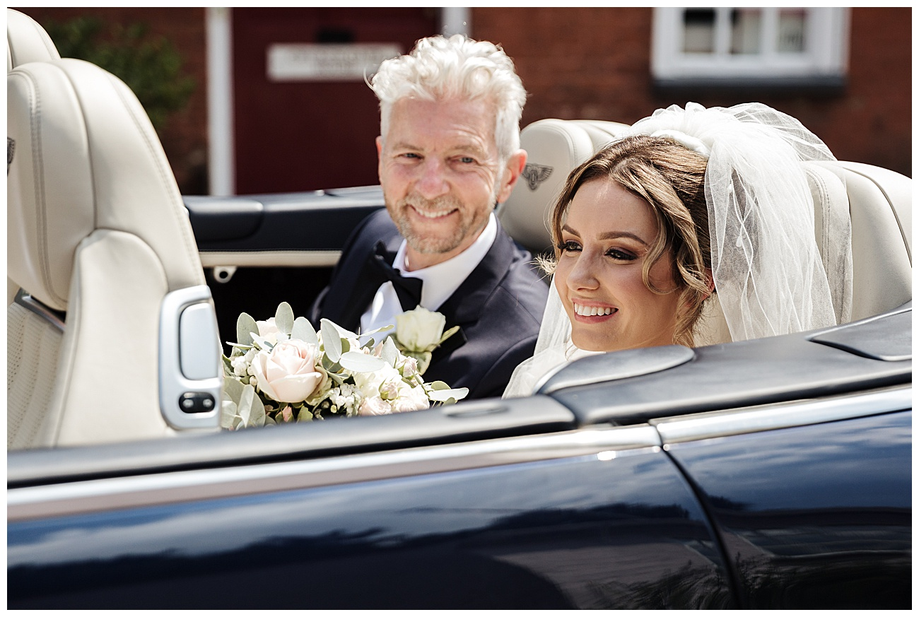 Dad looks at his daughter as they arrive in the wedding car