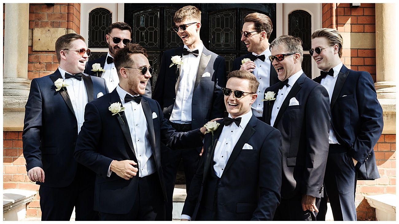 Groomsmen laugh outside their hotel