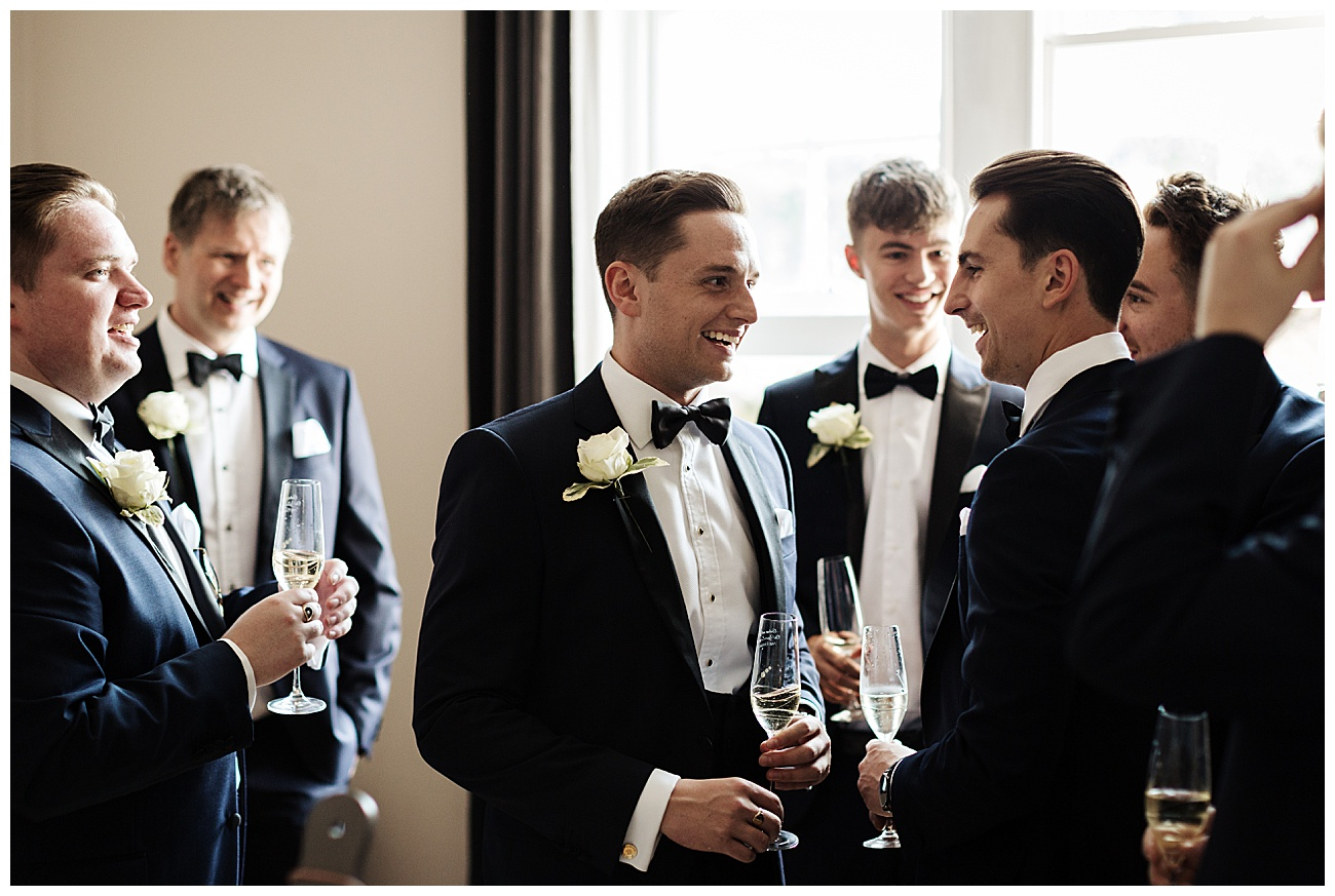 Groomsmen enjoy a joke drinking champagne