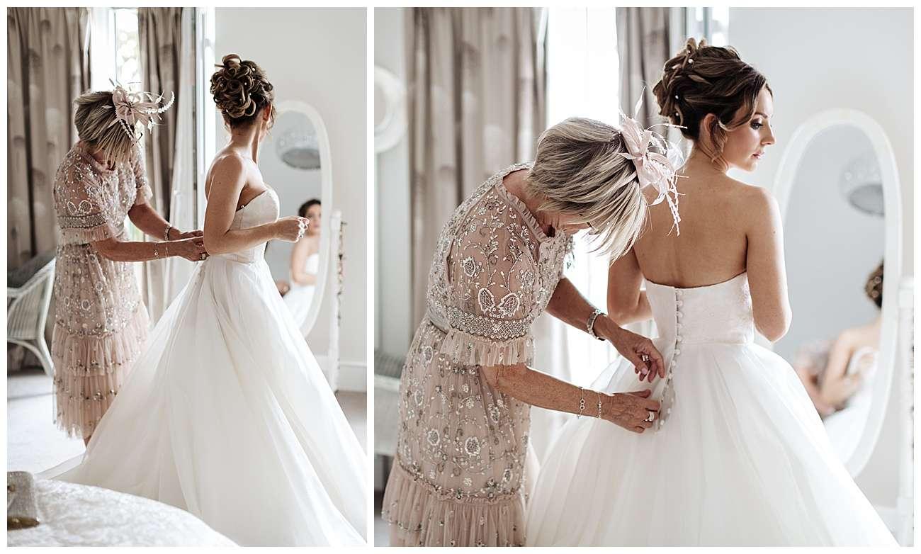 Brides mum doing brides wedding dress up at the back