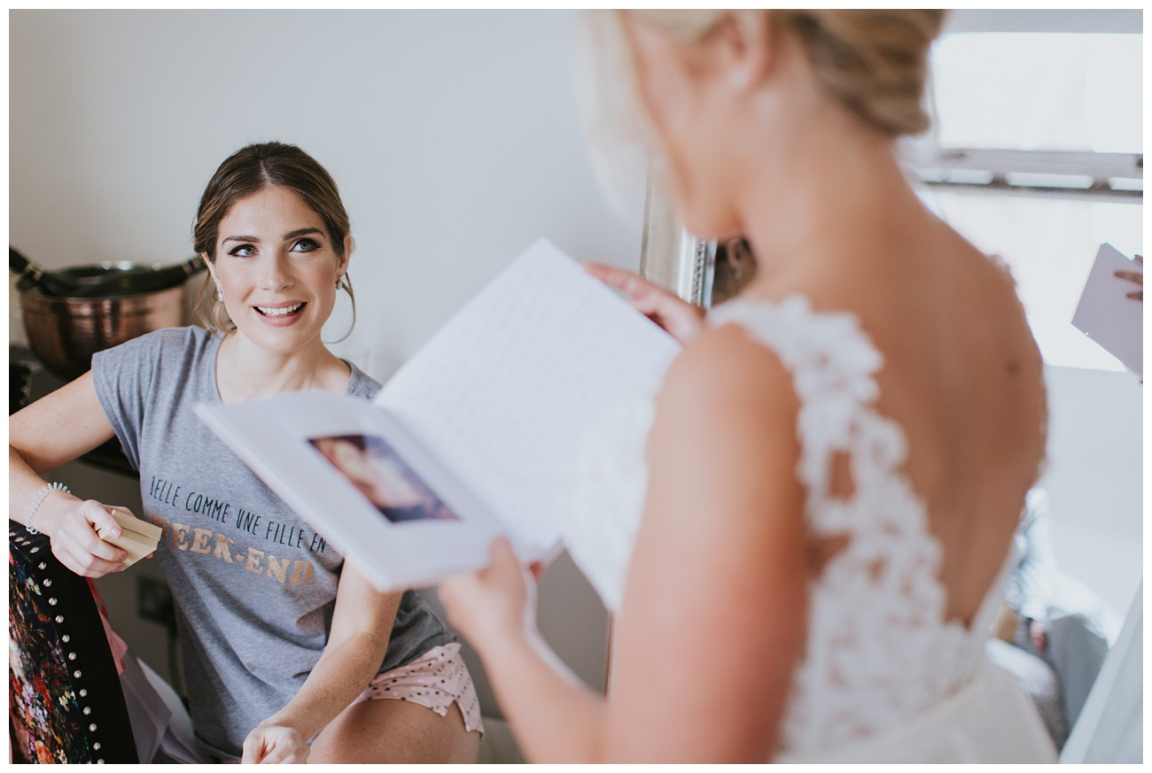 A bridesmaid watches the bride open a memory book. A gift from all the bridesmaids in the bridal cottage