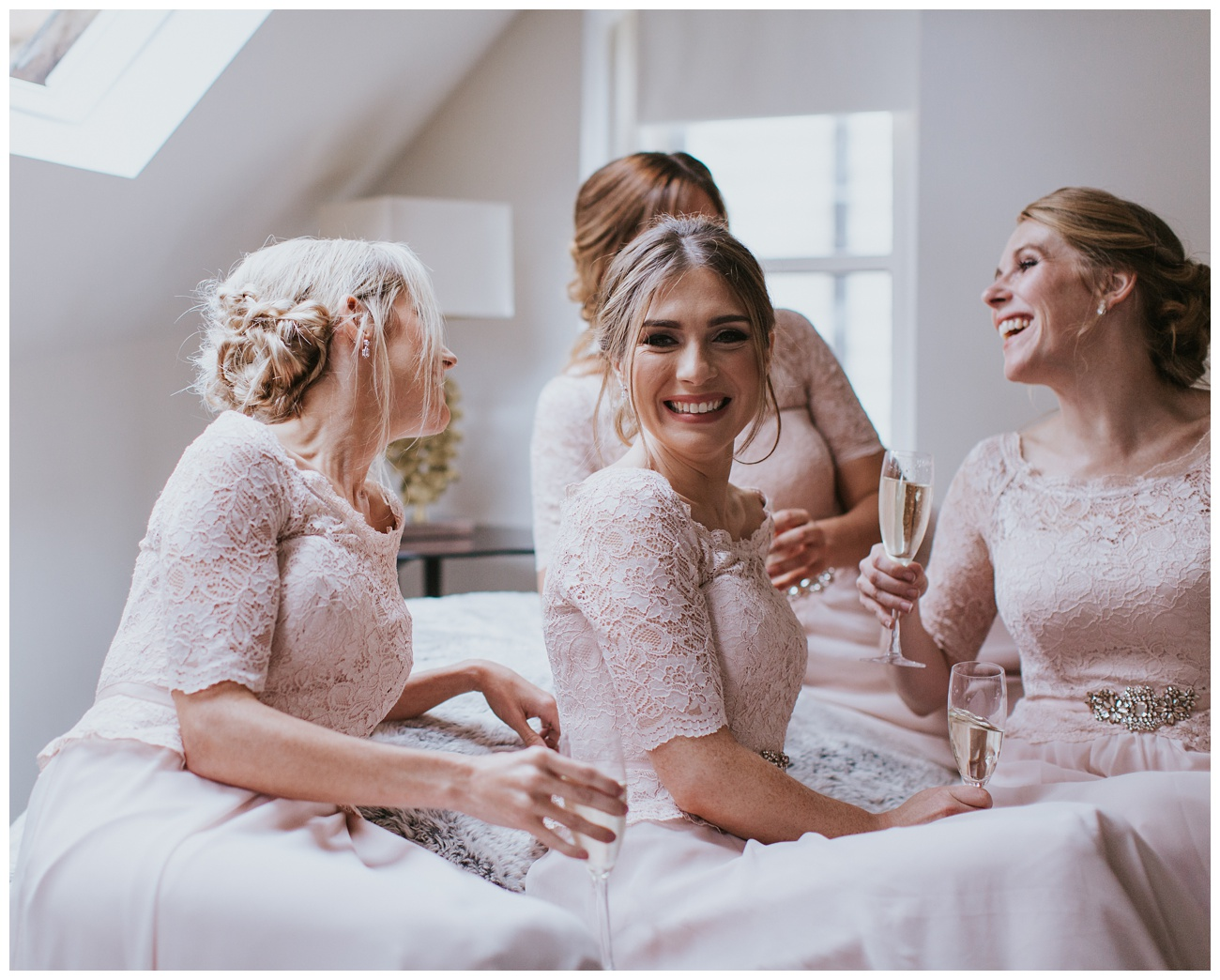 The bridesmaids laugh and drink champagne inside the bridal cottage