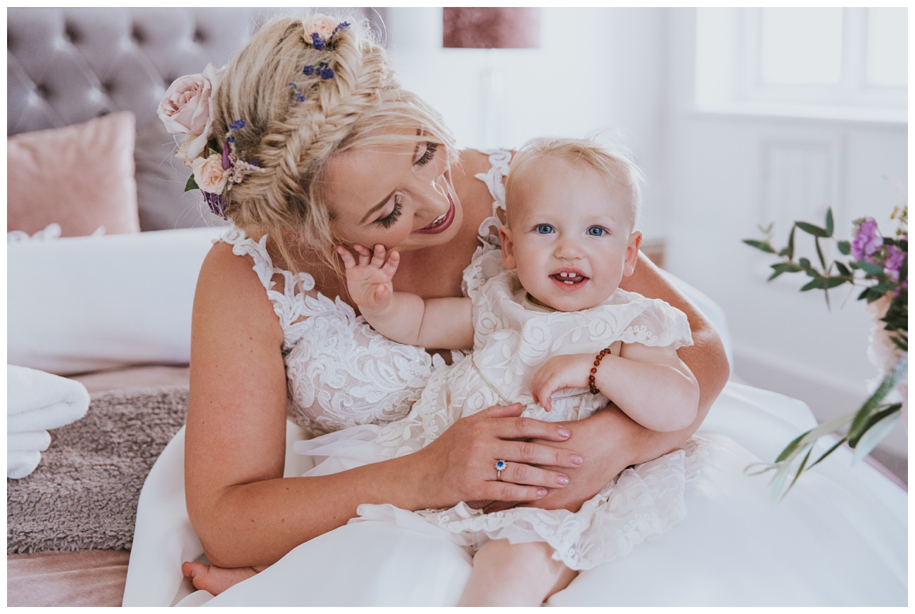 The bride holds her baby on the bed and laughs inside the bridal cottage
