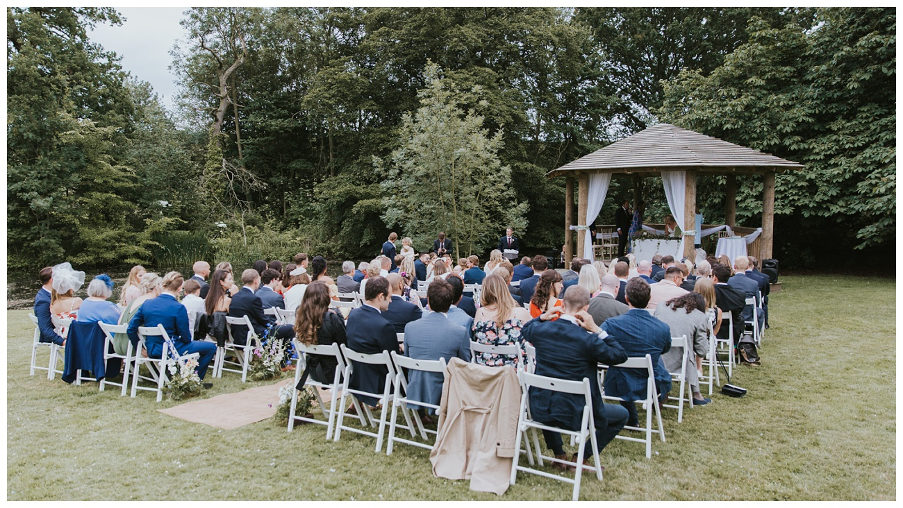 A view of all the wedding guests seated at the outdoor ceremony