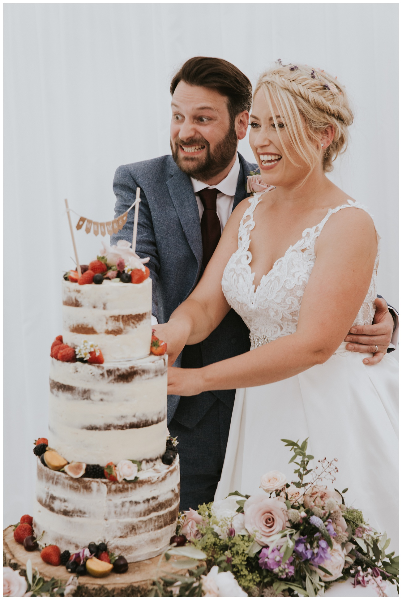 The bride and groom find it funny when they cut their wedding cake
