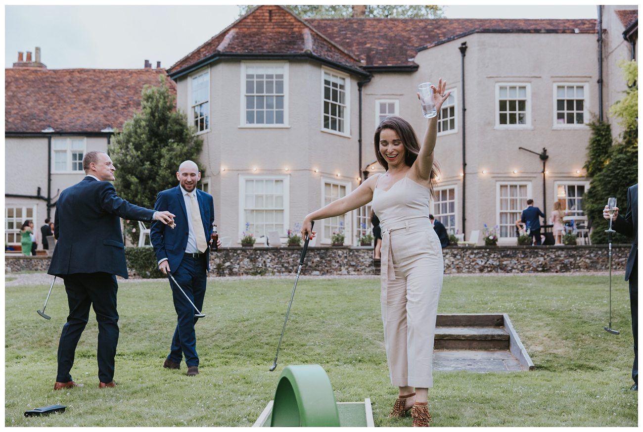 A wedding guest celebrates while playing crazy golf on the lawn