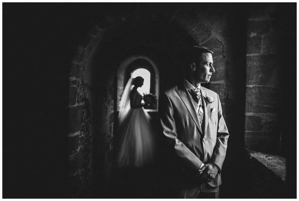 A black and white portrait of the groom in the foreground and the bride in the background in the castle