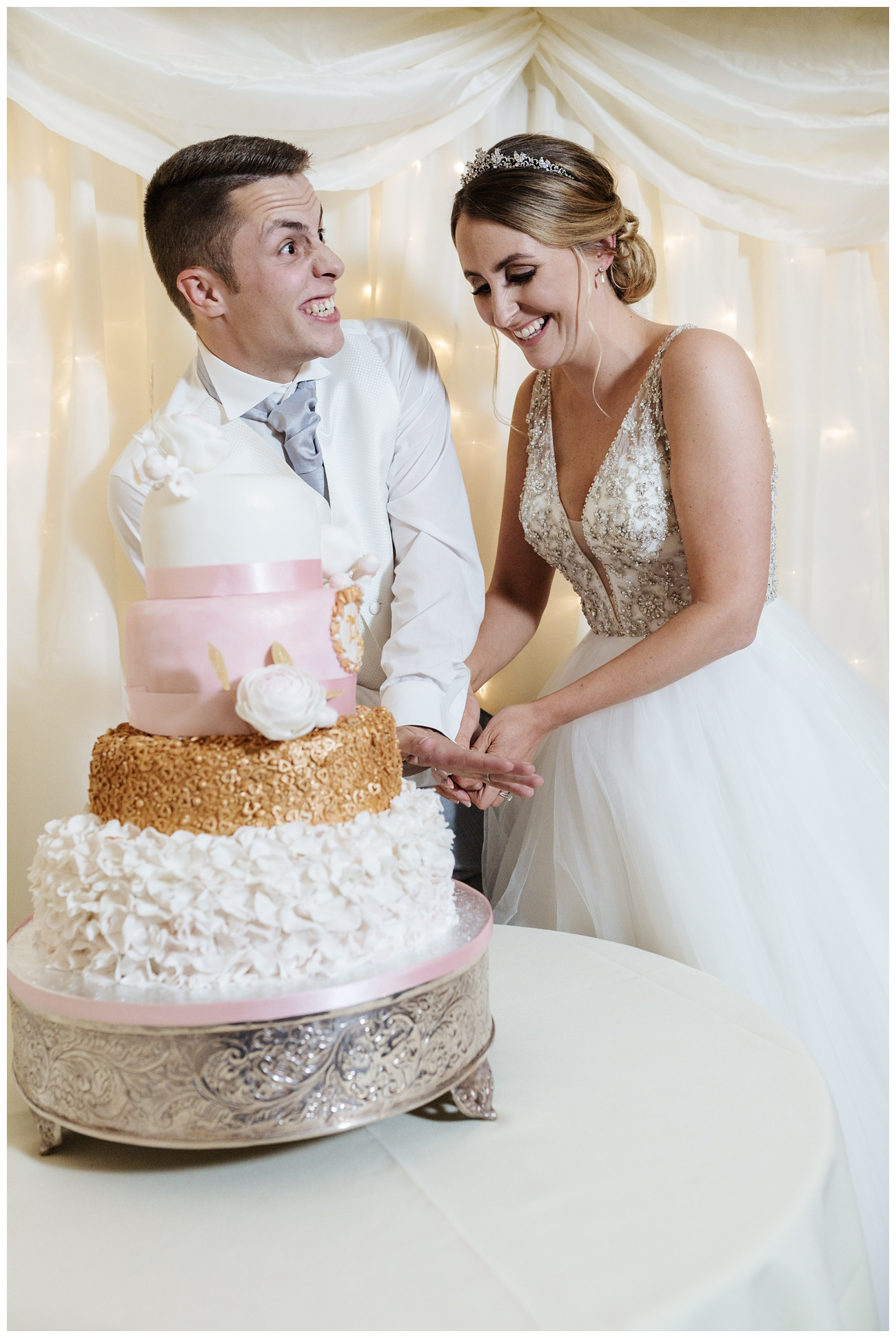 Fun shot of the bride and groom laughing cutting their wedding cake