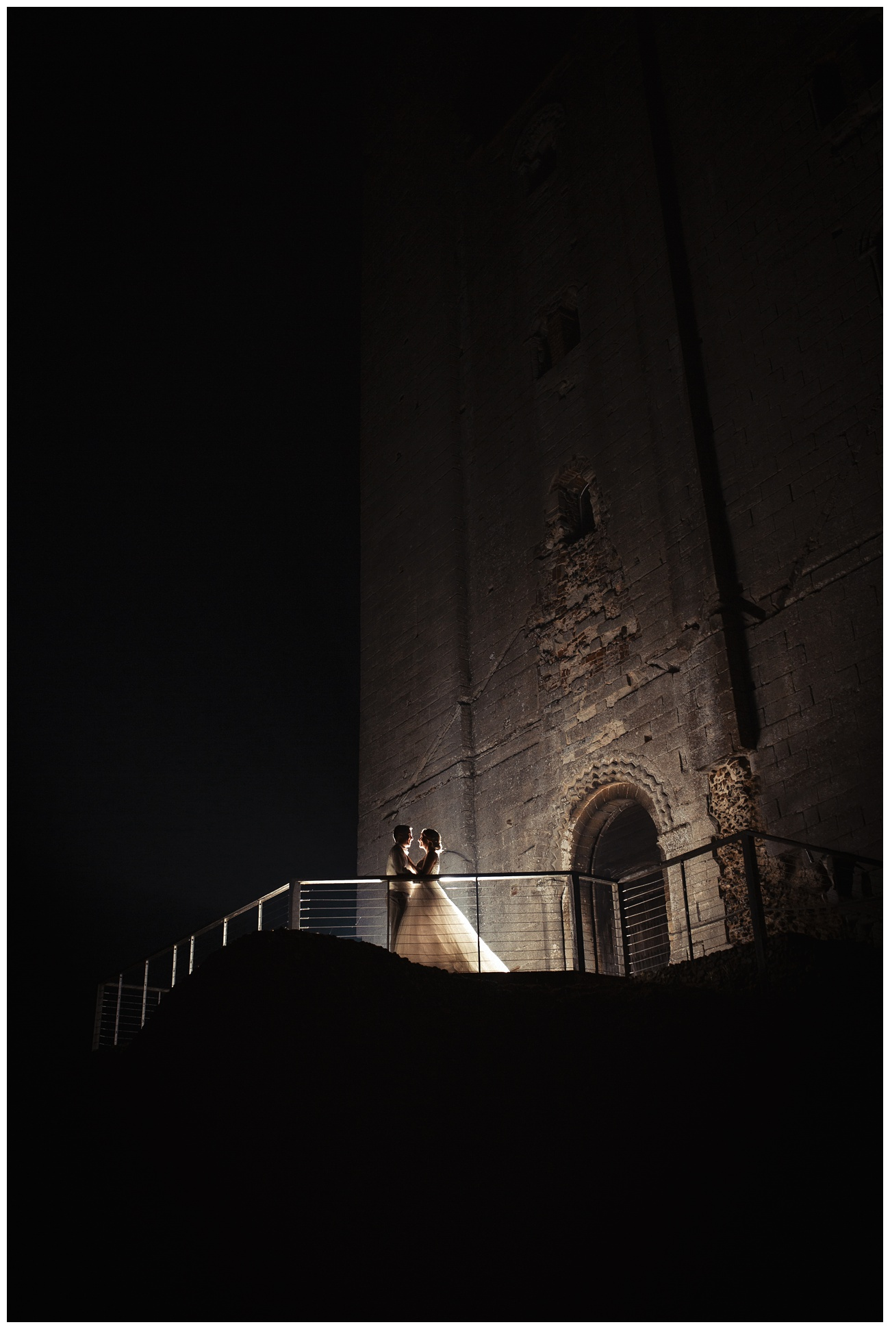 The bride and groom holding each other outside the castle at night