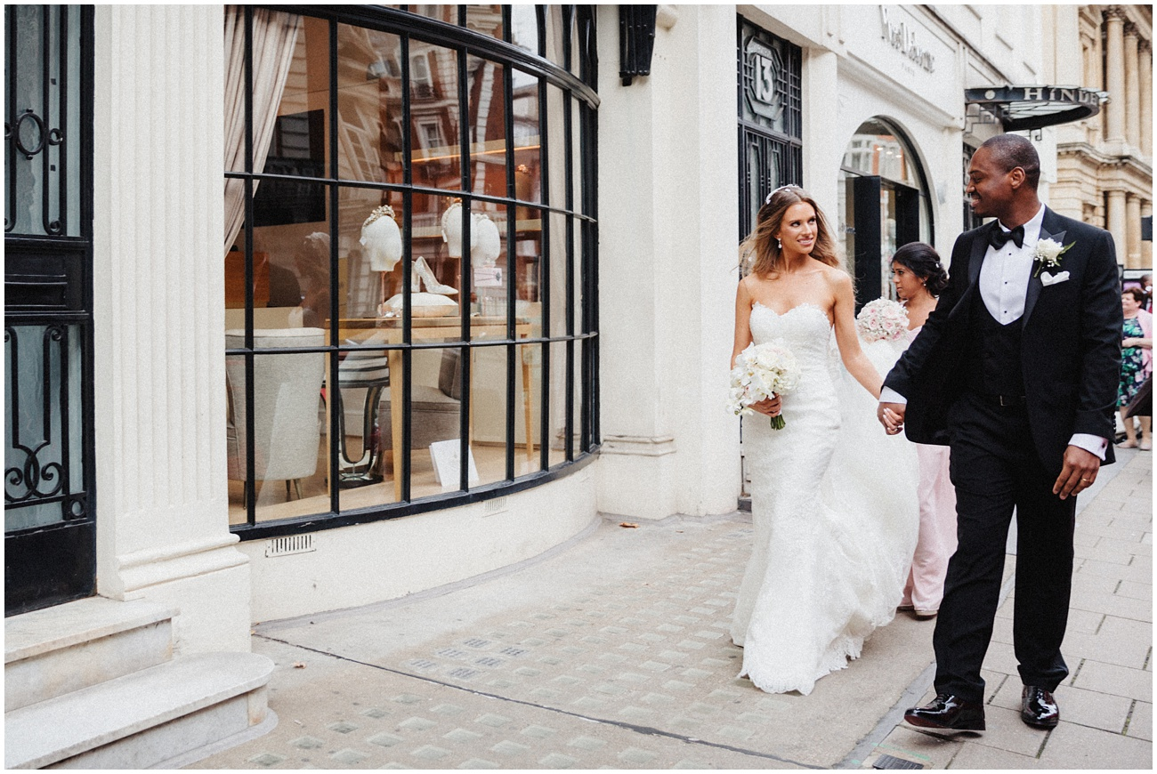 The bride and groom smile at each other as they walk past a London Boutique hand in hand